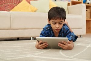 Boy lying on floor and reading something on digital tablet