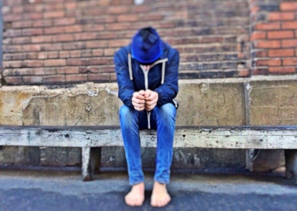 Bullied teen sitting on cement slab on city street