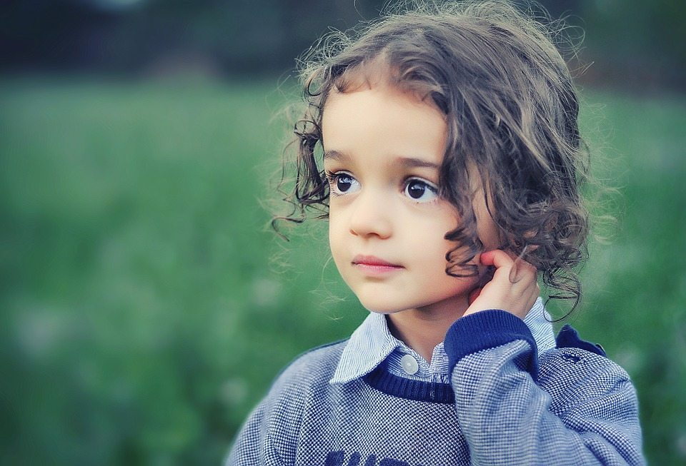 Brown-haired child in a field of grass