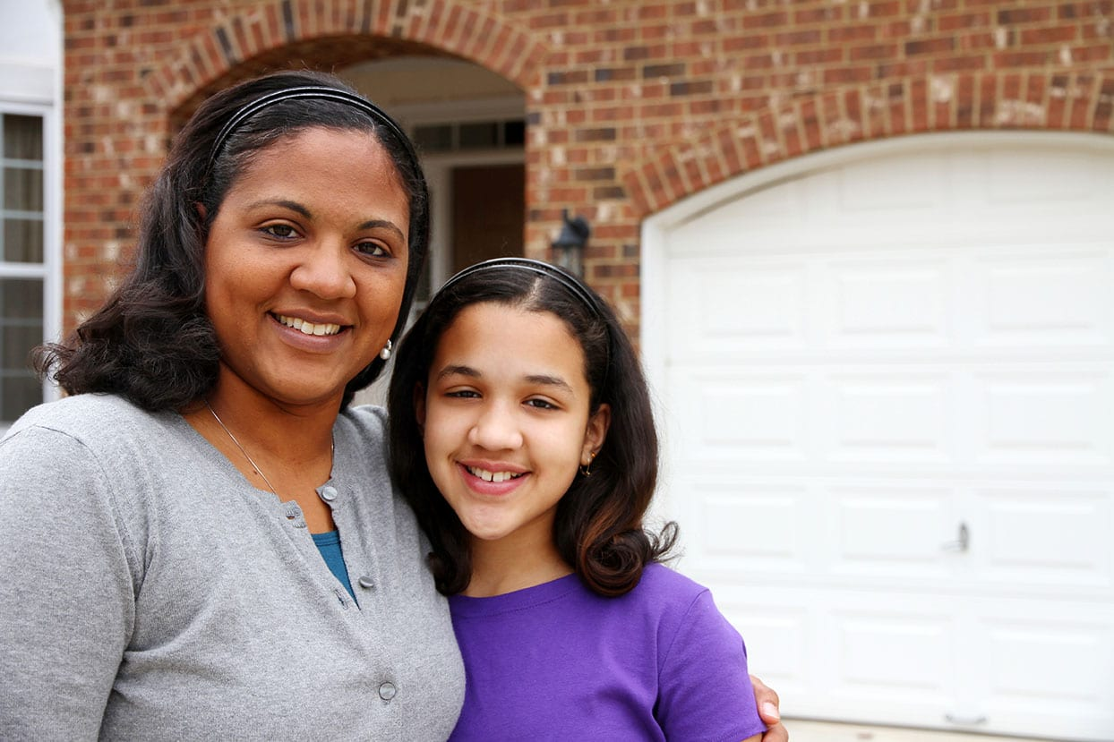 A mixed race mother and daughter at their home